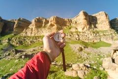 Sirva la búsqueda de la dirección con un compás en su mano en el punto de vista de las montañas del verano Búsqueda de la direcci foto de archivo