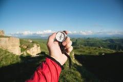 Sirva la búsqueda de la dirección con un compás en su mano en el punto de vista de las montañas del verano Búsqueda de la direcci fotos de archivo