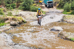 Sirva la bicicleta del montar a caballo, travesía el río en las montañas de Guate Fotografía de archivo libre de regalías