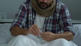 Sirva la bufanda que lleva que siente la garganta dolorida, tomando píldoras con agua, tratamiento frío almacen de video