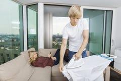 Sirva la camisa que plancha mientras que mujer que se relaja en el sofá en casa Fotografía de archivo libre de regalías