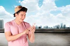 Sirva la camisa y el sombrero que llevan usando su teléfono móvil Fotografía de archivo libre de regalías