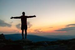 Sirva la celebración de la puesta del sol que mira la visión en montañas fotografía de archivo