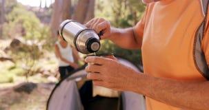 Sirva la colada del agua potable en taza en el sitio para acampar almacen de metraje de vídeo