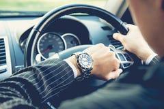 Sirva la conducción de un coche y la mirada del reloj imagenes de archivo