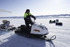 Sirva la conducción de una moto de nieve en un fondo de las extensiones extensas de Imagen de archivo libre de regalías