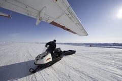 Sirva la conducción de una moto de nieve en un fondo de las extensiones extensas de Fotografía de archivo libre de regalías