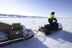 Sirva la conducción de una moto de nieve en un fondo de las extensiones extensas de Fotografía de archivo