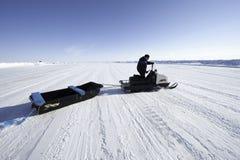 Sirva la conducción de una moto de nieve en un fondo de las extensiones extensas de Fotos de archivo libres de regalías