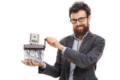 Sirva la destrucción de un billete de banco del dólar en una trituradora de papel Foto de archivo libre de regalías
