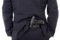 Sirva la disimulación del arma en los pantalones detrás el suyo detrás aislados en blanco fotos de archivo