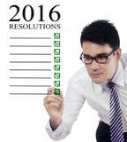 Sirva la elaboración de una lista de las resoluciones del negocio para 2016 Foto de archivo libre de regalías