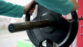 Sirva la eliminación de las placas de barbell después de entrenamiento activo del levantamiento de pesas en el gimnasio metrajes