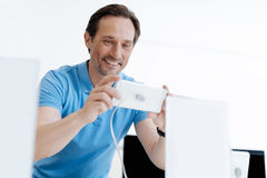 Sirva la emisión mientras que juega con el teléfono móvil en la tienda Fotografía de archivo libre de regalías
