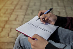 Sirva la escritura de la mano del ` s en el cuaderno, sketchbook al aire libre Imágenes de archivo libres de regalías