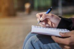 Sirva la escritura de la mano del ` s en el cuaderno, sketchbook al aire libre Imagen de archivo
