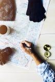 Sirva la escritura de la mano del ` s en mapa con los accesorios del viaje en tabl de madera Imagen de archivo libre de regalías