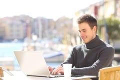 Sirva la escritura en un ordenador portátil en una cafetería Foto de archivo libre de regalías