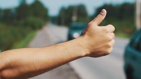 Sirva la estancia en el camino con el pulgar para arriba en día soleado del verano hitchhiking Viajero almacen de video