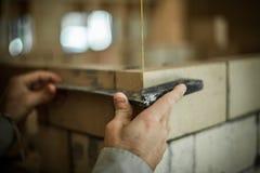 Sirva la fabricación de medidas mientras que trabaja en su pared de ladrillo imagen de archivo libre de regalías