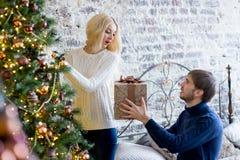 Sirva la fabricación de un regalo a la muchacha mientras que están adornando la Navidad Fotos de archivo