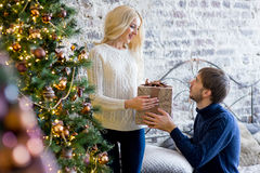 Sirva la fabricación de un regalo a la muchacha mientras que están adornando la Navidad Fotos de archivo libres de regalías