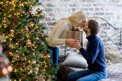 Sirva la fabricación de un regalo a la muchacha mientras que están adornando la Navidad Imágenes de archivo libres de regalías