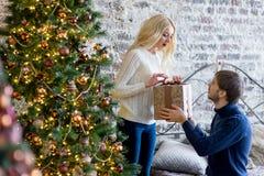 Sirva la fabricación de un regalo a la muchacha mientras que están adornando la Navidad Foto de archivo libre de regalías
