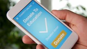 Sirva la fabricación de una donación en línea a la educación usando el uso de la caridad en smartphone almacen de metraje de vídeo