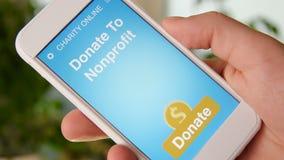 Sirva la fabricación de una donación en línea a la organización sin ánimo de lucro usando el uso de la caridad en smartphone metrajes