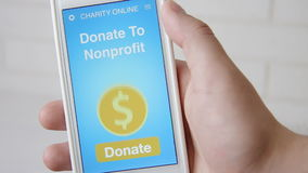 Sirva la fabricación de una donación en línea a la organización sin ánimo de lucro usando el uso de la caridad en smartphone almacen de metraje de vídeo