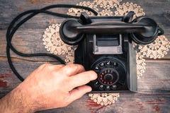 Sirva la fabricación de una llamada en un teléfono rotatorio Imágenes de archivo libres de regalías
