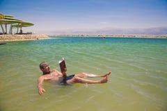 Sirva la flotación y lee un libro en el mar muerto imagen de archivo