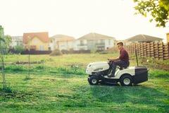 sirva la hierba del corte del trabajador con el cortacésped, concepto del lawncare Detalles industriales Imagen de archivo libre de regalías
