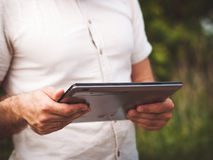 Sirva la lectura de la tableta digital al aire libre, cerca para arriba Fotografía de archivo libre de regalías