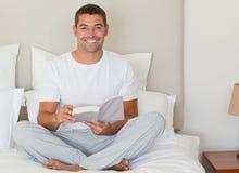 Sirva la lectura de un libro en la cama Fotos de archivo