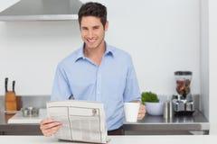 Sirva la lectura de un periódico y sostener una taza de café Imagen de archivo