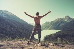 Sirva la levitación de salto del vuelo con el lago y las montañas en el concepto feliz de las emociones del viaje de la forma de  imagenes de archivo