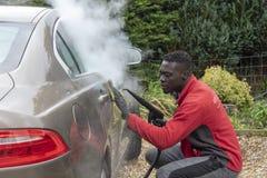 Sirva la limpieza de vapor el exterior de un coche de lujo imagen de archivo