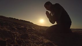 Sirva la luz del sol de rogación de la silueta del sol de la puesta del sol de dios que se sienta la religión Imagen de archivo