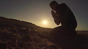 Sirva la luz del sol de rogación de la silueta del sol de la puesta del sol de dios que se sienta la religión Foto de archivo