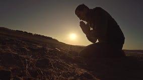 Sirva la luz del sol de rogación de la silueta del sol de la puesta del sol de dios que se sienta la religión Fotos de archivo libres de regalías