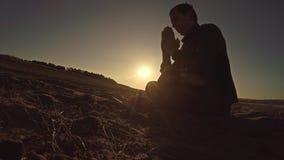 Sirva la luz del sol de rogación del sol de la silueta de dios de la puesta del sol que se sienta la religión Imágenes de archivo libres de regalías