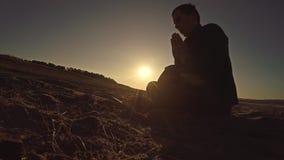 Sirva la luz del sol de rogación del sol de la silueta de dios de la puesta del sol que se sienta la religión Imagen de archivo libre de regalías