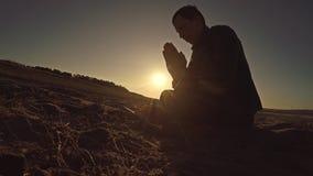 Sirva la luz del sol de rogación del sol de la silueta de dios de la puesta del sol que se sienta la religión Imagen de archivo