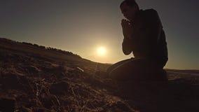 Sirva la luz del sol de rogación del sol de la silueta de la puesta del sol de dios que se sienta la religión Fotografía de archivo libre de regalías