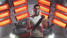 Sirva la máscara protectora y los vidrios que llevan que sostienen la máquina pulidora con las luces calientes rojas en fondo almacen de video