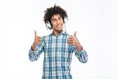 Sirva la música que escucha en auriculares y el mostrar los pulgares para arriba Fotos de archivo
