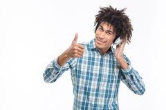 Sirva la música que escucha en auriculares y el mostrar pulgar para arriba Fotografía de archivo