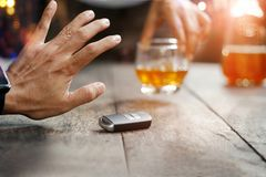 Sirva la mano con llave del coche en la tabla que rechaza el alcohol de consumición imagen de archivo libre de regalías